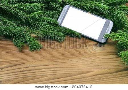 Mobile phone with blank white screen laying in fir tree branches on burnt wooden board surface background with copy space. Christmas decorations.