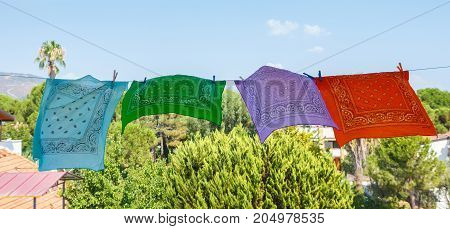 Four Colored Bandanas Hang On Rope In The Street