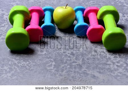Barbells In Different Colors And Apple Placed In Pattern, Closeup