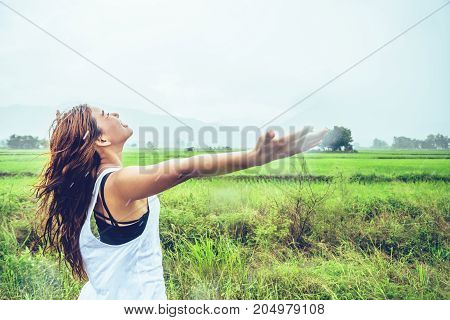 Asian women travel relax in the holiday. Stand in a meadow in the rain. On the meadow During the rainy season.Thailand