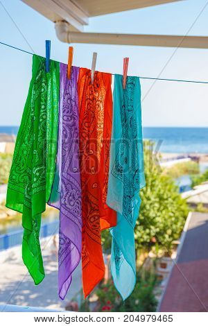 Four Colorful Bandanas Hang On Rope In The Street