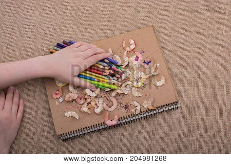 Hand Holding Color Pencils Over A Notebook
