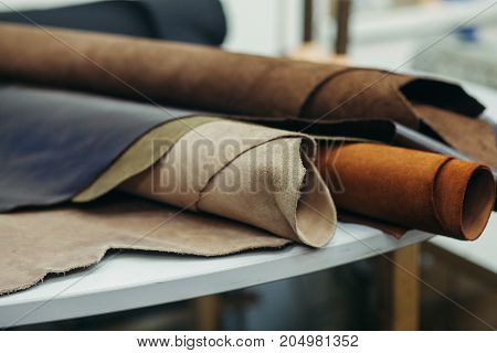 Brightly colored leather in rolls on the white wooden background. Leather craft