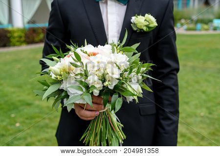 Bridal Wedding Bouquet Of White Flowers And Greenery With Ribbons In Groom Hand. Groom Waiting For B