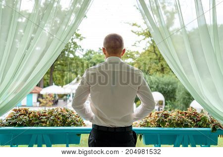 Back View Of Young Man Dressed In White Shirt And Black Trousers On Porch Outdoor, Free Space. Groom