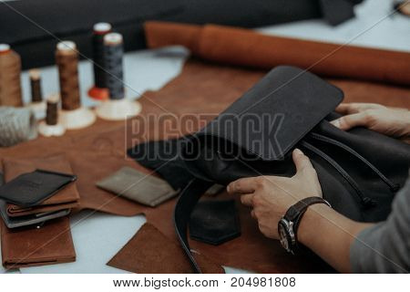 The master makes a leather bag. A close up, a product from skin in hands. Handwork