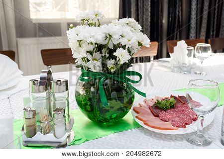 Bouquet Of White Chrysanthemums In Round Glass Vase With Green Ribbon On Dinner Table, Free Space. W