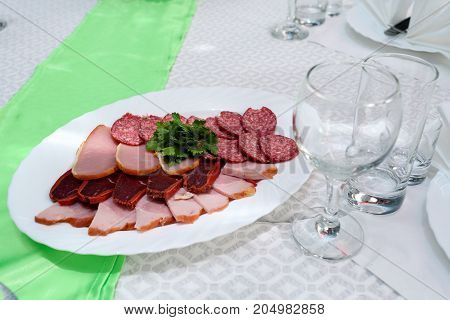 Cold meat plate with delicious sliced ham salami meat and parsley on celebratory dinner table selective focus. Meat platter with selection on wedding banquet