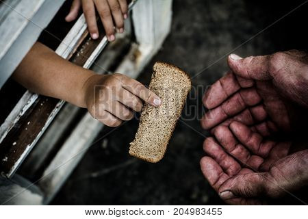In his hand clutching a piece of bread. The bread passed through the window.