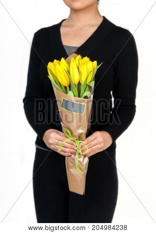 woman holds bouquet of yellow tulips. Valentine's Day