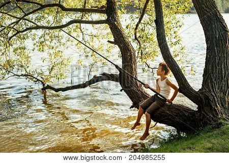 a young boy is fishing while sitting on a tree branch over a river