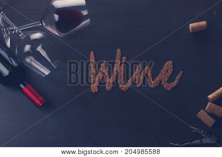 Bottle of red wine and two wine glasses on table with wine word letters, retro toned
