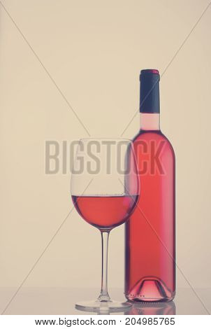 High glass with still rose wine and wine bottle, retro toned