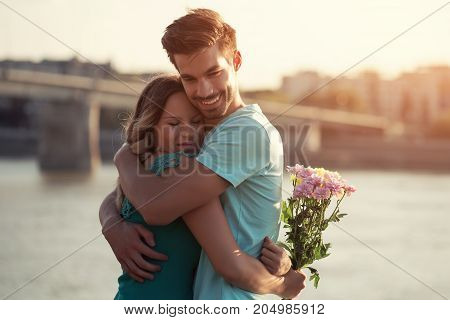 Young man is giving beautiful bouquet of flowers to his girlfriend.