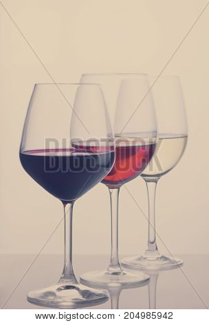 Row of three wine glasses with red, white and rose wine, retro toned