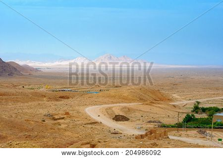 view from the mountain opening on the stony desert mountain tops tower on the horizon Iran