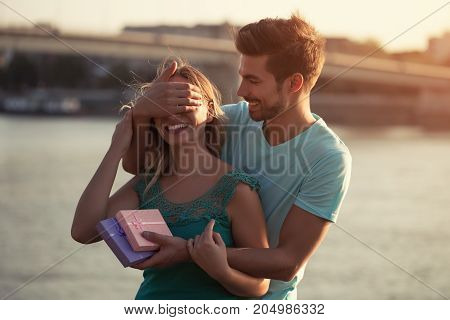 Young man is giving present to his beautiful girlfriend.
