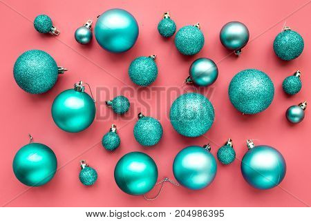 Christmas toys. Blue balls on pink background top view.