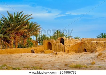 village from orange clay left by people with a palm grove at sunset