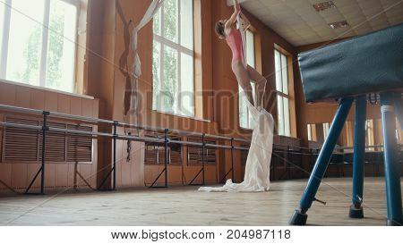 Young girl acrobat shows flexibility on gymnastic hoop, telephoto shot