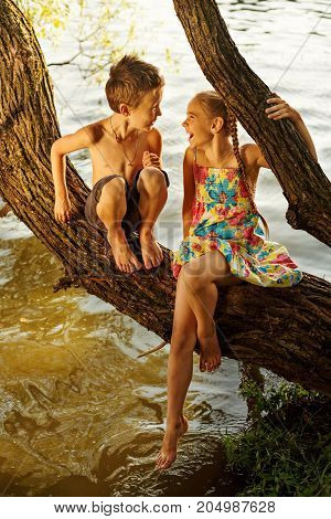 naughty boy and girl sitting on a branch over water, laughing out loud, having fun talking