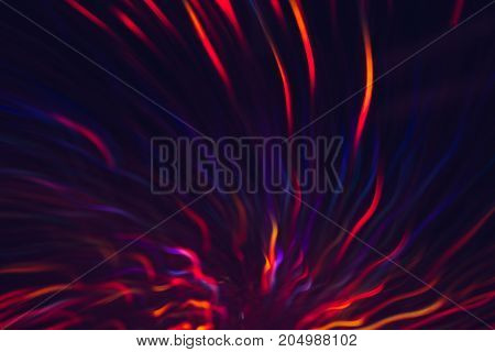 Abstract background of colorful lines in motion on black. Bokeh of defocused blue, and red curves, blurred neon leds, festive backdrop of holidays, fireworks and celebrations