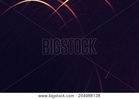 Abstract background of yellow lines in motion on black wallpaper. Bokeh of defocused curves, blurred neon leds, festive or business backdrop of city lights and banners