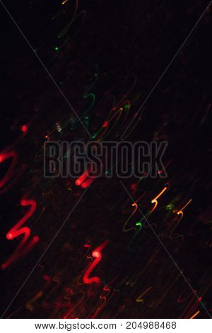 Abstract background of colorful crankles in motion on black. Bokeh of defocused curves, blurred neon yellow, green and red leds, festive backdrop of fireworks, holidays and celebrations
