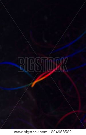 Abstract background of colorful lines in motion on black. Bokeh of defocused curves, blurred neon blue and red leds, festive or business backdrop of serpantine, holidays and celebrations
