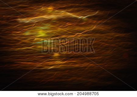 Abstract background of blurred yellow lines in motion similar to sunset haze. Bokeh of defocused crankles, blurred neon leds, shimmering and glare lights of sunbeams through clouds