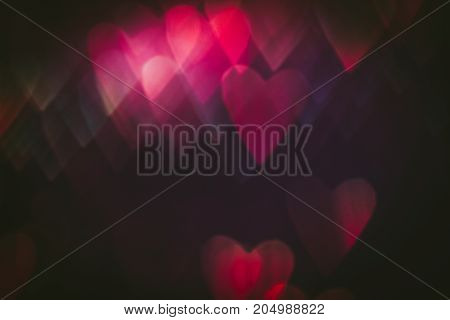 Abstract background of colorful hearts on black backdrop. Bokeh of defocused glitters, blurred pink symbols of love. Festive wallpaper of holidays and celebrations, St. Valentine's day