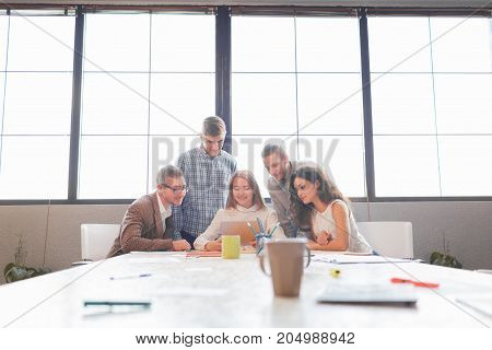 Business people showing team work while working in office interior. People helping one of their colleague to finish new business plan. Business concept.