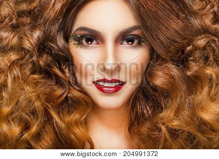 Close-up portrait of a beautiful young woman model with glamor make-up and bulk hair