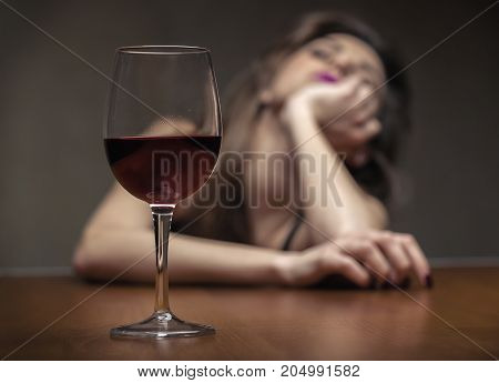 Woman in depression drinking alcohol. Focus on the glass