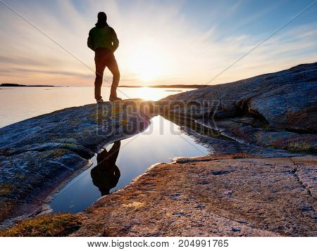 Silhouette Man On Cliff Above Sea. Tourist Stand Alone On Rock And Watch Sea Horizon