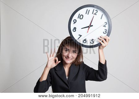Young Asian Business Woman Show Ok With A Clock.