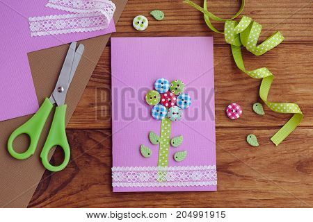 Nice greeting card made by a kid for mothers day, fathers day, March 8, birthday. Handmade card with a flower from wooden buttons. Stationery on a wooden table. Children workshop concept. Top view