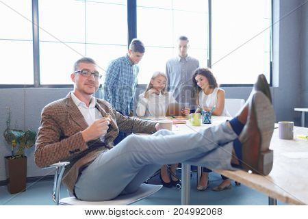 Sassy and confident businessman with legs on the table on the office meetup background. Smart and young boss in glasses.
