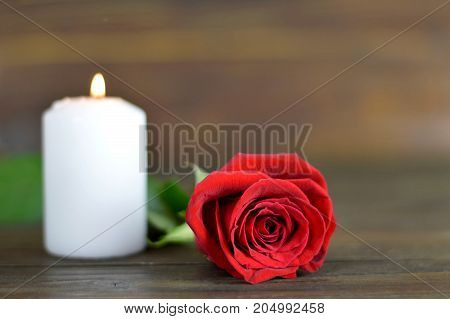 Candle and red rose on wooden background