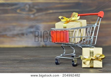 Shopping cart with Christmas gift boxes on wooden background