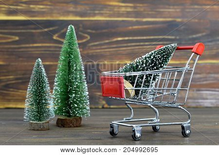 Shopping cart with Christmas tree on wooden background