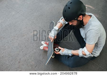 Professional skater checks his skateboard after training. Extreme sport challenge and competition, skateboarder safety equipment and urban lifestyle of young people background with free space