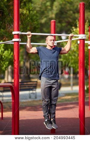 Attractive young man working out on crossbars in a park on a blurred background. Strong, fit man doing push-ups on horizontal bars.