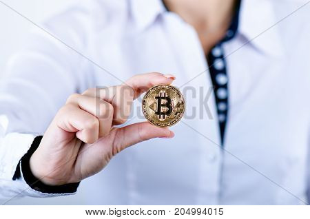Businesswoman holding bitcoin isolated on a white background.Golden bitcoin coins in women's hands. Virtual currency. Crypto currency. New virtual money.