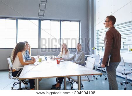 Young speaker on a business training with students on a classroom background. People listening to a start-up meeting in a conference room. Copy space.