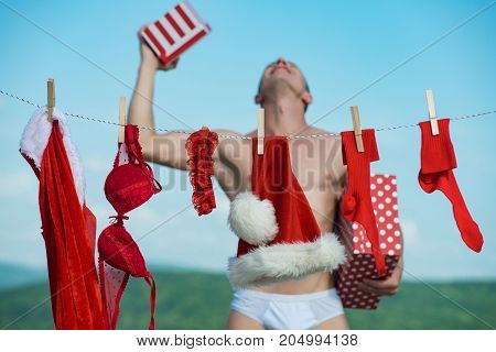 Christmas man with happy face hold present box. New year guy with muscular body on blue sky. Santa claus man hanging clothes for drying. Laundry and dry cleaning. Xmas red costume on rope with pin.