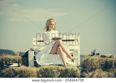 Summer holidays and vacation. Woman reading book on bench on blue sky. Student with camera and typewriter on hay. Girl in straw wreath and white dress on sunny day. Hobby and lifestyle concept.