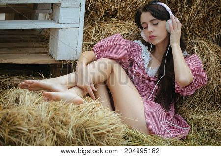 Girl listening music with closed eyes. Summer vacation concept. Leisure and entertainment. Lifestyle and technology. Woman with headphones relaxing in hay.