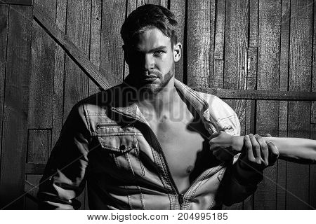 One sexy young stylish handsome muscular lover macho man with beard in jacket with bare chest and female mistress hand undressing him standing indoor in studio on wooden backdrop horizontal photo