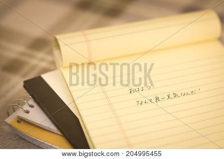 Japanese; Learning New Language Writing Greetings On The Notebook